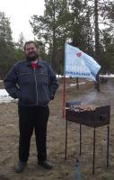 Михаил на фоне флага и мангала